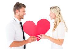 拿着红色心脏的有吸引力的年轻夫妇 库存照片