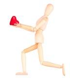 拿着红色心脏的木钝汉 免版税库存图片