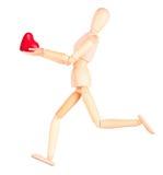拿着红色心脏的木钝汉 免版税库存照片