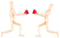 拿着红色心脏的木钝汉 库存图片