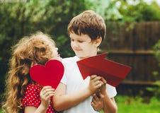 拿着红色心脏的逗人喜爱的孩子在夏天公园塑造 华伦泰 库存图片