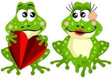 拿着红色心脏的逗人喜爱的青蛙夫妇 图库摄影