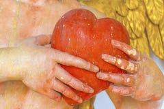 拿着红色心脏的雕象的手 免版税库存照片