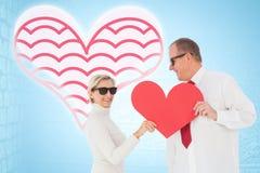 拿着红色心脏的更旧的富感情的夫妇的综合图象塑造 库存图片