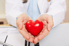 拿着红色心脏的医生的手 免版税库存照片