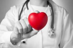 拿着红色心脏的医生 免版税库存照片
