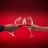 拿着红色敬酒酒的夫妇玻璃 库存照片