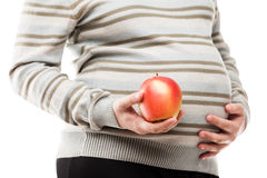 拿着红色未加工的成熟苹果果子的孕妇手 库存照片