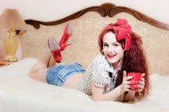 拿着红色杯子热的有红色嘴唇的饮料性感的画报女孩美丽的红头发人少妇和钉子愉快微笑在床上 免版税库存图片
