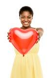 拿着红色气球心脏华伦泰的逗人喜爱的非裔美国人的妇女 免版税图库摄影