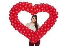 拿着红色气球心脏的微笑的妇女 图库摄影