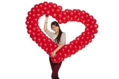 拿着红色气球心脏的微笑的妇女 免版税库存图片