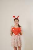 拿着红色气球心脏的逗人喜爱的滑稽的女孩 图库摄影