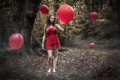 拿着红色气球的十几岁的女孩在有漂浮的B有薄雾的森林里 免版税库存图片