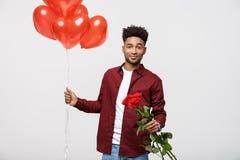 拿着红色气球的年轻可爱的人和为惊奇起来了他的女朋友 免版税库存图片