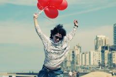 拿着红色气球的美丽的妇女 免版税图库摄影