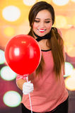 拿着红色气球的逗人喜爱的女孩小丑笑剧特写镜头画象  免版税库存图片