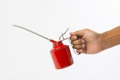 拿着红色油罐头的手 免版税图库摄影
