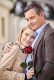 拿着红色玫瑰和微笑对照相机的白肤金发的妇女 库存照片