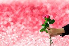 拿着红色玫瑰的手在红灯欢乐模糊和b开花 免版税库存图片