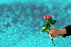 拿着红色玫瑰的手在蓝色光欢乐模糊开花和 免版税图库摄影