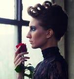 拿着红色玫瑰的美丽的端庄的妇女 免版税图库摄影