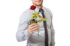 拿着红色玫瑰的英俊的人 免版税图库摄影