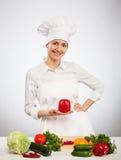 拿着红色甜椒的愉快的年轻人厨师 图库摄影