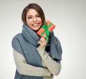 拿着红色礼物的冬天围巾的微笑的女孩 与te的大微笑 库存图片