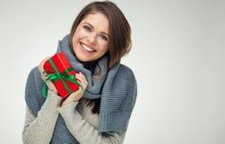 拿着红色礼物的冬天围巾的微笑的女孩 与te的大微笑 免版税库存图片