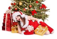 拿着红色礼物盒的圣诞老人帽子的圣诞节女孩。 免版税库存照片