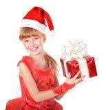 拿着红色礼物盒的圣诞老人帽子的孩子。 免版税库存照片