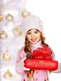 拿着红色礼物盒的帽子和手套的孩子在白色圣诞节树附近。 免版税图库摄影