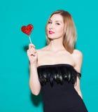 拿着红色糖果心脏的时兴的美丽的女孩 在绿色背景的一件黑礼服在演播室 方式秀丽女孩 免版税库存图片