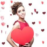 拿着红色纸心脏的快乐的少妇 免版税库存照片