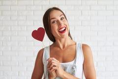 拿着红色纸心脏的愉快的美丽的妇女 库存照片