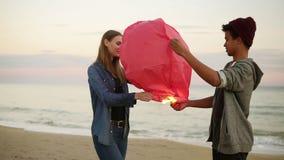 拿着红色纸灯的年轻不同种族的夫妇在发射前 在海滩的浪漫日期 可爱的妇女 影视素材
