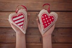 拿着红色纺织品心脏的孩子移交一张木桌 库存照片