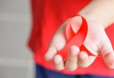 拿着红色艾滋病了悟丝带的孩子手 库存图片