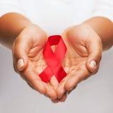 拿着红色艾滋病了悟丝带的手 免版税库存照片