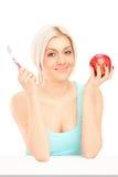 拿着红色苹果和牙刷的美丽的白肤金发的妇女 库存图片
