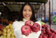 拿着红色苹果的少妇手中在市场商店 免版税库存照片