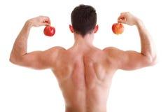 拿着红色苹果的运动性感的男性身体建造者 图库摄影