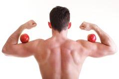 拿着红色苹果的运动性感的男性身体建造者 免版税库存照片