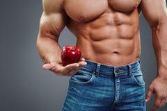 拿着红色苹果计算机的坚强的肌肉人 库存照片