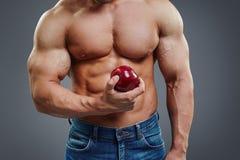 拿着红色苹果计算机的坚强的肌肉人 图库摄影