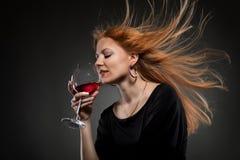 拿着红色葡萄酒杯妇女的头发 库存图片