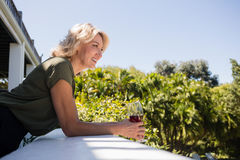 拿着红色葡萄酒杯的白肤金发的妇女在阳台上在餐馆 免版税图库摄影