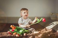 拿着红色郁金香并且微笑一个逗人喜爱的小男孩的画象 男孩坐一条棕色毯子 在框架的太阳强光 温暖的colo 图库摄影