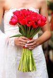 拿着红色郁金香的手婚姻花束 免版税库存图片